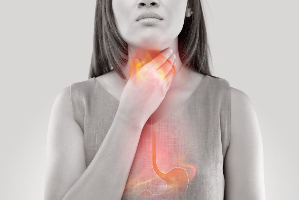 woman holding her throat due to acide reflux